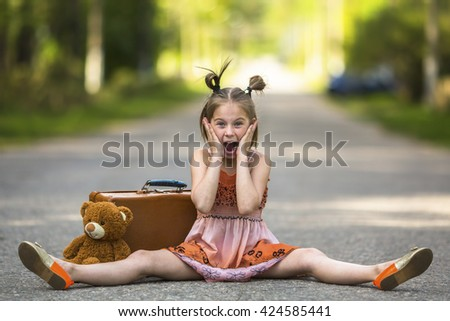 Little girl sitting on the road with a suitcase and a Teddy bear. - stock photo