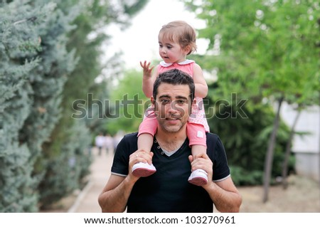 Little girl sitting on the shoulders of her father in the park - stock photo