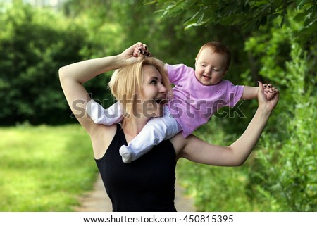 Little girl sitting on the shoulders of moms, have fun, play, jump, whirl in the Park Sunny summer day outdoors - stock photo