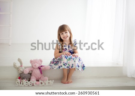 little girl sitting on the steps with toys - stock photo