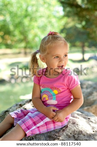 Little girl sitting on the stone in the park and laughing - stock photo