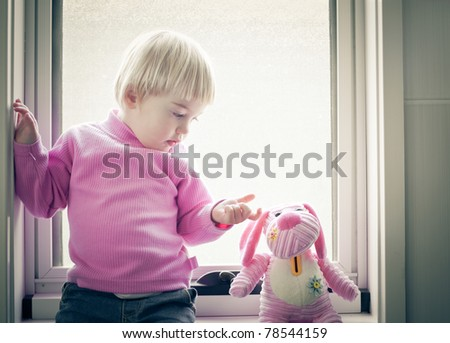 Little girl sitting on the window pane looking at her favorite toy - stock photo
