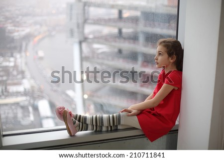 Little girl sitting on the windowsill of a large window on a cloudy day - stock photo