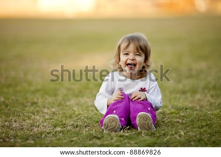 little girl sitting, playing in grass, laughing - stock photo