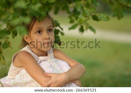 Little girl sitting under a tree in nature