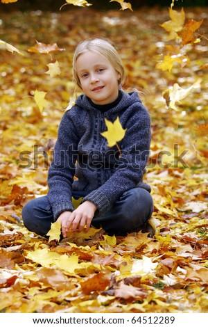 Little girl sitting under falling leaves in autumn park - stock photo