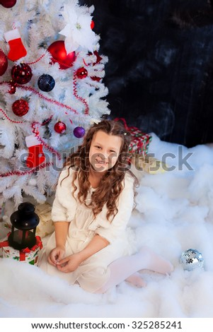 Little girl sitting under the Christmas tree; adorable girl smiling nearby Christmas tree; white fir-tree decorated with red balls and socks - stock photo