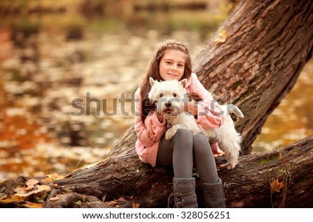 little girl  sitting under the tree and  holding her white small dog on the hands in the autumn park  - stock photo