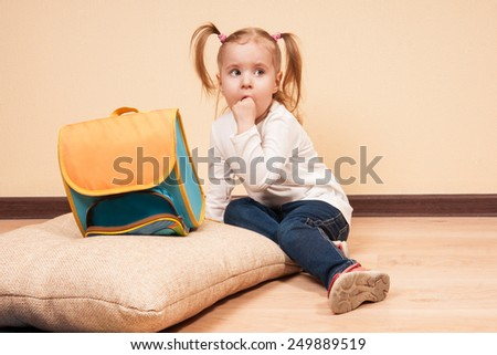 Little girl sitting with a finger in her mouth on a floor with a big school bag near by, horizontal studio shot - stock photo