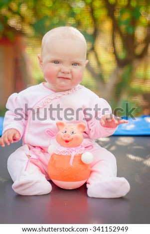 little girl sitting with a toy - stock photo