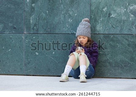 little girl sitting with her phone, portrait - stock photo