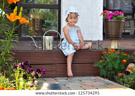 little girl sitting with watering can - stock photo