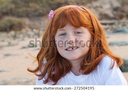 little girl, six years old, with front tooth missing smiling and showing the gap - stock photo