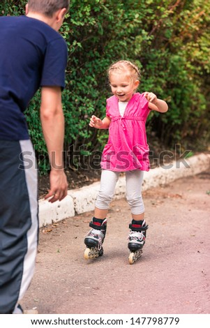 Little girl skating on roller skates at park, first attempt - stock photo
