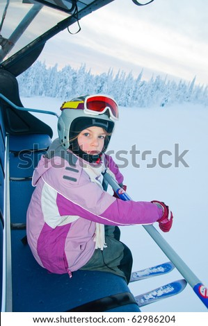 Little girl-skier on the ski lift watching the sunrise at a ski resort in Finland - stock photo