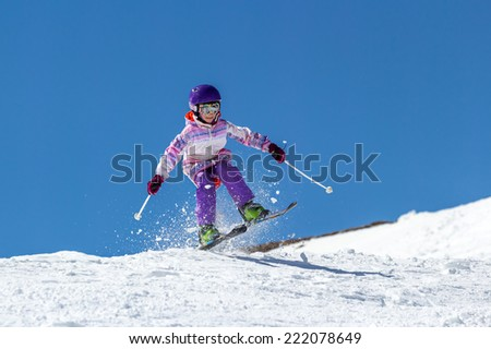 Little girl skier soars over a slope in a jump on a background of clear sky
