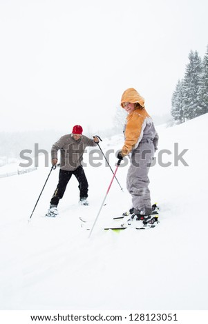 Little girl skies with her father together - stock photo