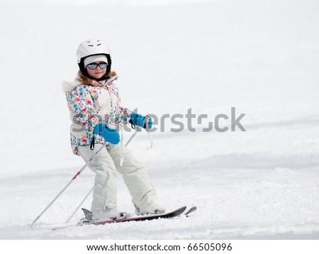 Little girl skiing downhill -  ( space for text) - stock photo