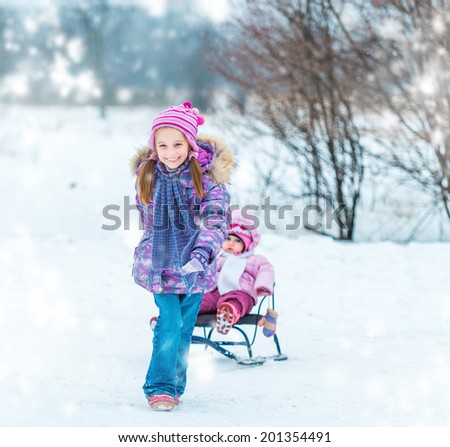 little girl sledding his sister in the winter park - stock photo