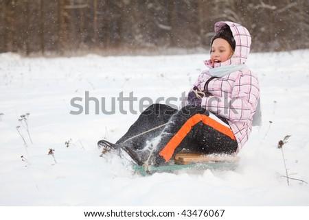Little girl sledging down hill, bright winter scene - stock photo