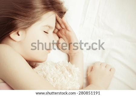 little girl sleep with teddy-bear, vintage color - stock photo