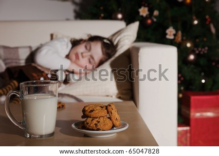 Little girl sleeping, and waiting for Santa Claus with a glass of milk and cookies - stock photo