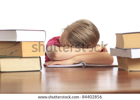 Little girl sleeping behind a pile of books. (isolated on white background)