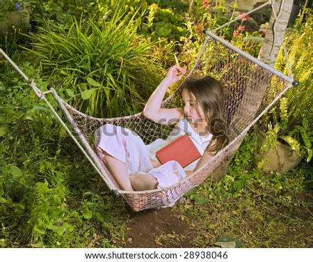little girl sleeping in a hammock with a book - stock photo