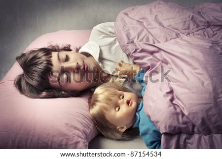 Little girl sleeping in bed with a doll - stock photo