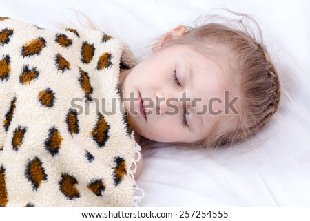 Little girl sleeping in her bed under a blanket spotted - stock photo