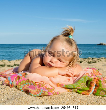 Little girl sleeping on beach near sea. - stock photo