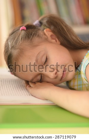 Little girl sleeping on book at home