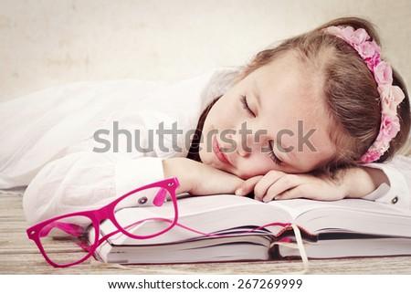 Little girl sleeping on the books - stock photo