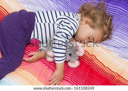 Little girl sleeping with her toy. - stock photo