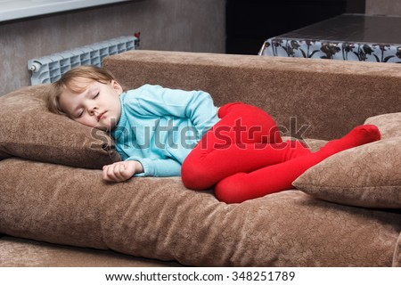 little girl sleeps like a top on a couch