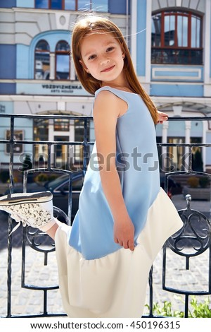 Little girl small baby pretty face wear fashion blue dress walk on sun city street building summer weather kid child young and beauty happy daughter play fun clothes collection