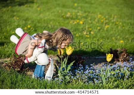 Little girl smelling flower in springtime. Allergy concept - stock photo