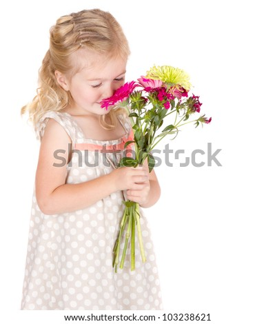 Little girl smelling flowers isolated on white
