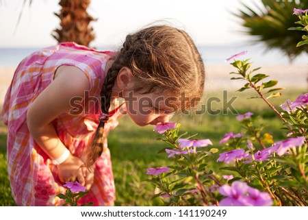 Little girl smelling flowers on the beach. Summer holidays. - stock photo