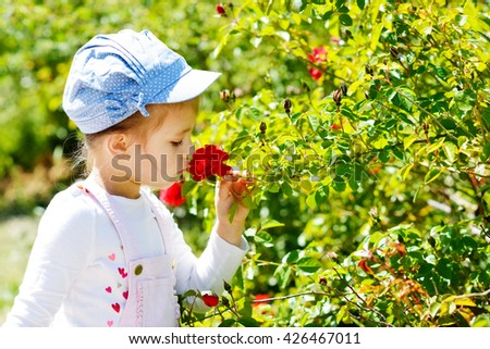 little girl  smelling rose in spring time - stock photo