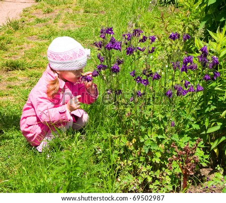 Little girl smells the wild flowers