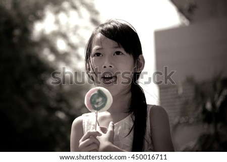 Little girl smile with sweet candy from low angle black and white style,dark tone - stock photo