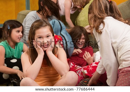 Little girl smiles at a sleepover with friends - stock photo