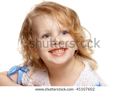 little girl smiles showing her teeth