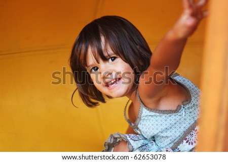 Little girl smiling and playing outdoors - stock photo