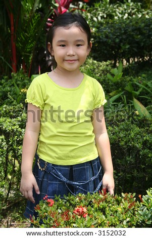 Little girl smiling and standing alone in the garden - stock photo