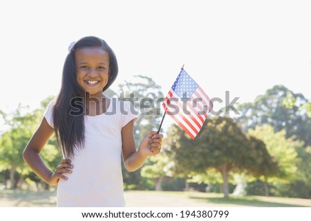 Little girl smiling at camera waving american flag on a sunny day - stock photo