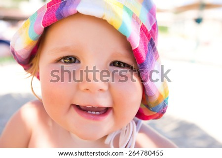 Little girl smiling at the beach in summer - stock photo