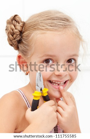 Little girl smiling, holding her missing tooth with pliers showing the gap - stock photo