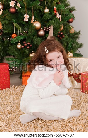 Little girl smiling in a front of Christmas-tree - stock photo